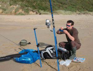Ce pêcheur monte sa canne en alignant les anneaux